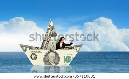 Successful businesswoman sailing on dollar boat in financial sea - stock photo