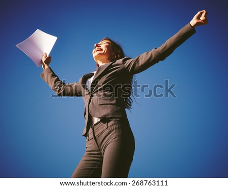 Successful  businesswoman showing success over blue sky - stock photo