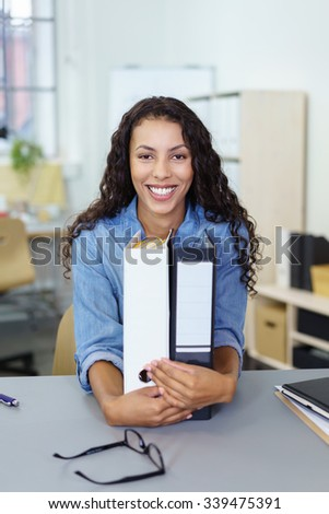 successful businesswoman sitting at the desk with arms around folders in the office