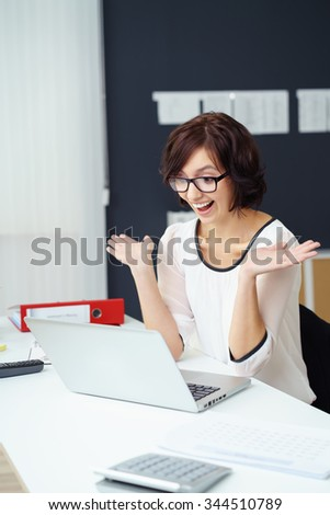 Successful Businesswoman Sitting at the Table with Laptop Computer, Showing Surprised Facial Expression. - stock photo