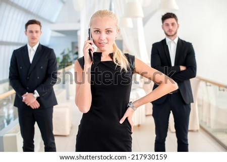 Successful businesswoman. Successful businessman standing in an office and looking at the camera with a mobile phone in her hand while her colleagues standing behind her