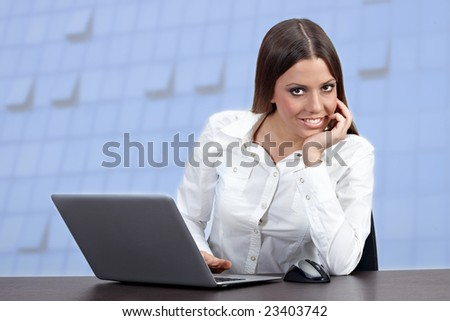 Successful businesswoman using laptop with modern building windows in background.