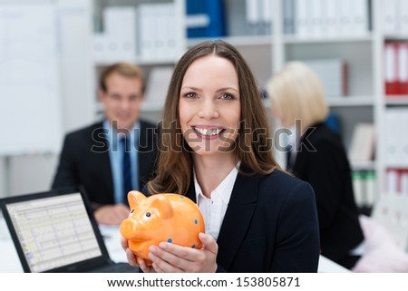 Successful businesswoman with a piggy bank cupped in her hands smiling at the camera as she plans her investments to meet her goals and fund her retirement - stock photo