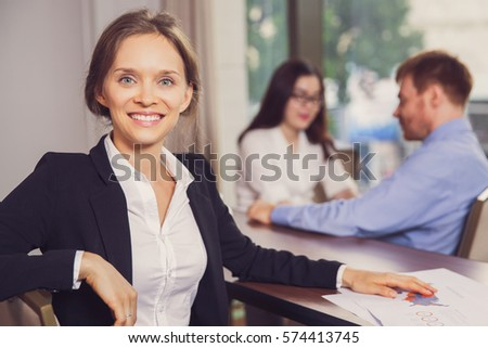 Successful Businesswoman with Colleagues in Office