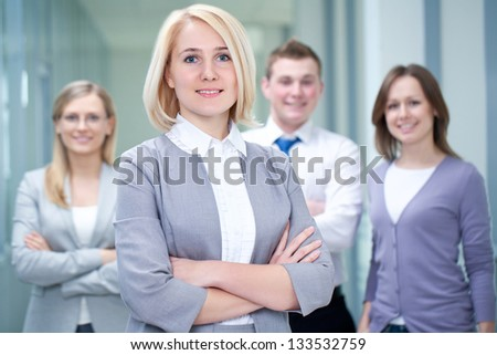 Successful businesswoman with colleagues in the background - stock photo