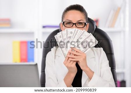 Successful businesswomen. Confident middle-aged woman sitting at her working place and holding money in her hands - stock photo