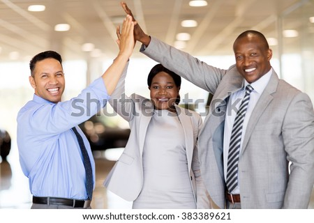 successful car dealership staff giving high five in showroom - stock photo