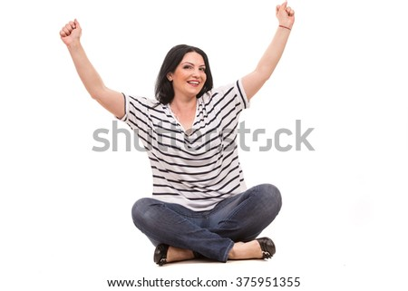 Successful casual woman sitting with legs crossed and raising her fists isolated on white background