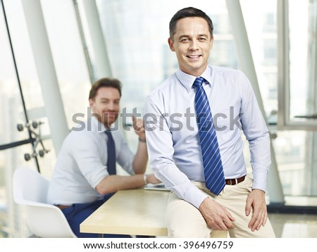 successful caucasian business leader sitting on desk in office smiling with colleague in background. - stock photo