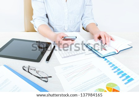 Successful caucasian businesswoman sitting at desk in casual clothes and planning her working day in the office - stock photo