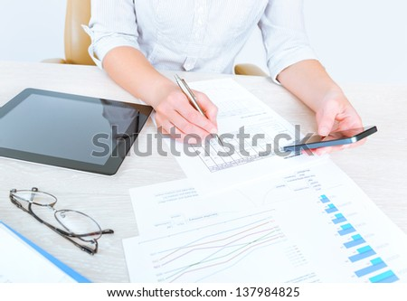Successful caucasian businesswoman sitting at desk in casual clothes and using modern devices for analyzing sales statistics for the month period of time - stock photo