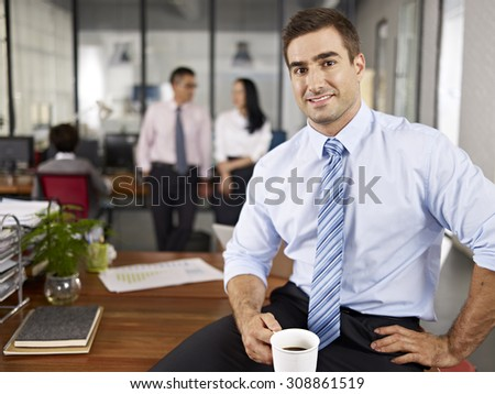 successful caucasian expat businessman sitting on desk in office with local colleagues talking in background. - stock photo