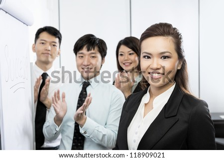 Successful Chinese business woman with her team clapping and congratulating her.