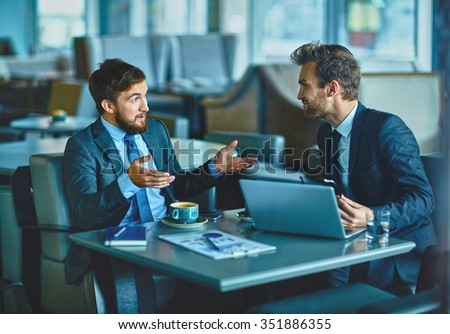 Successful colleagues having meeting in cafe - stock photo