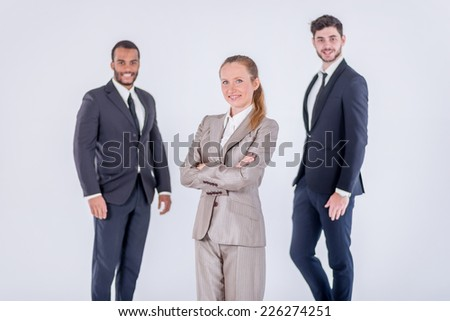 Successful colleagues. Three confident and successful businessman standing with hands clasped while waiting customer on isolated gray background - stock photo