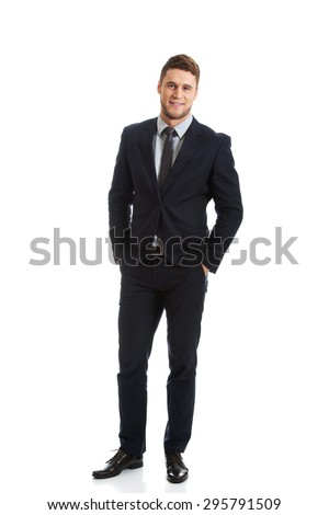 Successful confident businessman with hands in pockets. - stock photo