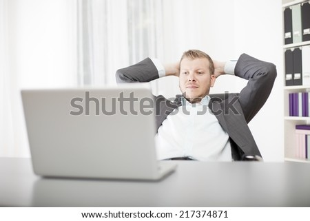 Successful confident young businessman sitting back in his chair at the office with his hands clasped behind his head and a satisfied expression - stock photo