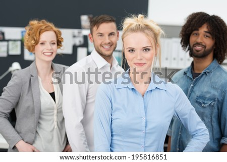 Successful confident young multiethnic business team led by an attractive young blond woman smiling happily as they pose for the camera - stock photo