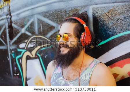 Successful cool deep house dj,hipster bearded men,standing with crossed arms with employee in background preparing his lunch.Music on big earphones,reflected sunglasses,abstract print t-shirt. - stock photo