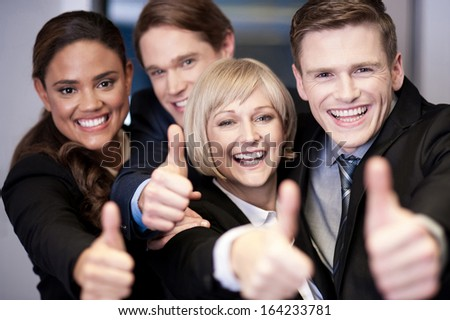 Successful corporate team showing thumbs up - stock photo