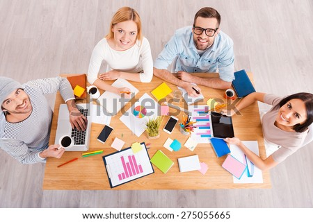 Successful creative team. Top view of group of business people in smart casual wear working together and smiling while sitting at the wooden desk  - stock photo