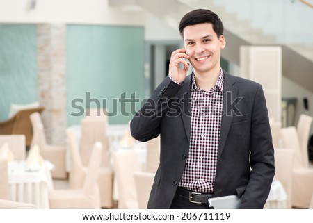 Successful deal over the phone. Young and confident businessman talking on a cell phone in hand and smiling directly at the camera - stock photo