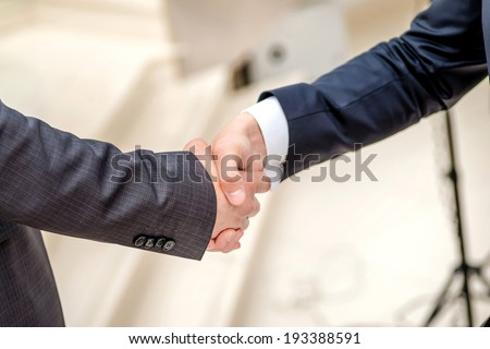 Successful deal! Two young businessman standing opposite each other and shake their hands. Young people smiling into the camera. Close-up view below
