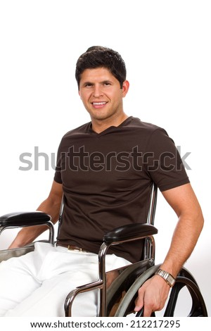 Successful disabled man sits in his wheelchair smiling. - stock photo