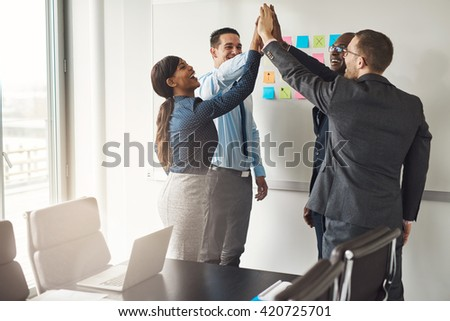 Successful diverse multiracial business team giving a high fives gesture as they celebrate in a conference room in an office - stock photo