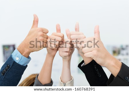 Successful diverse young business team giving a victorious thumbs up to show their success and motivation, close up view of their raised hands - stock photo