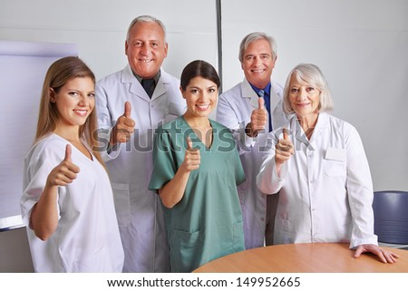 Successful doctor and MTA team holding their thumbs up - stock photo