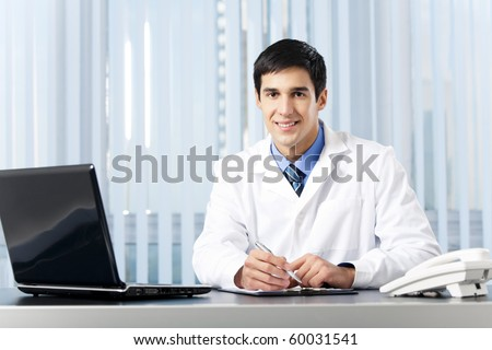 Successful doctor with laptop, at office - stock photo