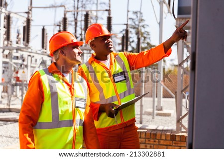 successful electrical engineers taking machine readings in substation - stock photo