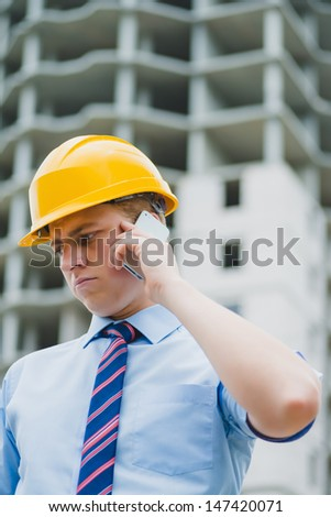 successful engineer in a helmet with a phone