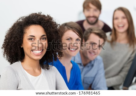 Successful enthusiastic multiethnic business team led by a beautiful young African American businesswoman posing together in a row with focus to the woman - stock photo