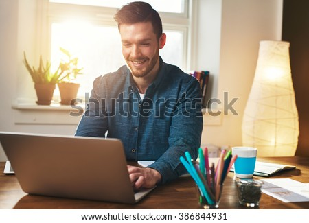 Successful entrepreneur smiling in satisfaction as he checks information on his laptop computer while working in a home office, sun flare behind - stock photo