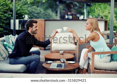 Successful entrepreneurs clinking cups for toast successful adoption of the agreement, business partners smiling while drinking coffee while discussing good idea, business people enjoying coffee break - stock photo