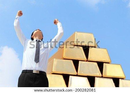 Successful excite business man standing with gold bullion - stock photo