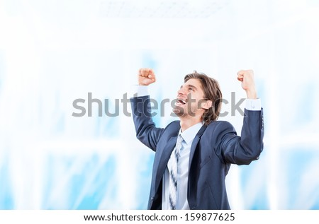 Successful excited business man happy smile hold fist gesture in bright blue office, handsome young businessman with raised hands arms, wear elegant suit and tie - stock photo