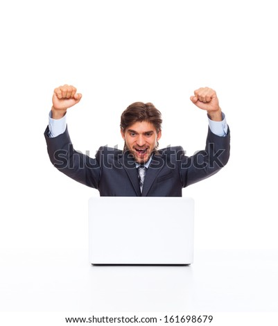 Successful excited business man with laptop happy smile hold fist up gesture, handsome young businessman with raised hands arms looking to computer, sitting at desk isolated over white background - stock photo