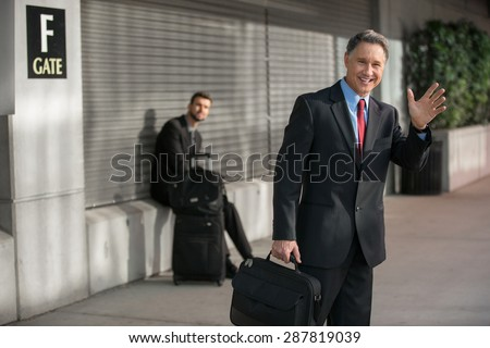 Successful executive man calls taxi cab after arriving from trip - stock photo