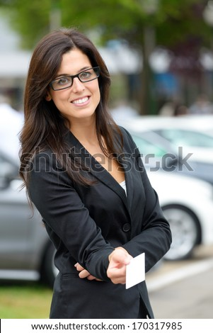 Successful female car sales representative giving blank business card  in luxury automobile trade fair. Beautiful brunette saleswoman outdoor. - stock photo