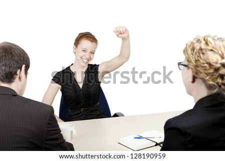 Successful female corporate job applicant rejoicing with her fist raised in the air as she smiles happily back at her two interviewers who are sitting with their backs to the camera - stock photo