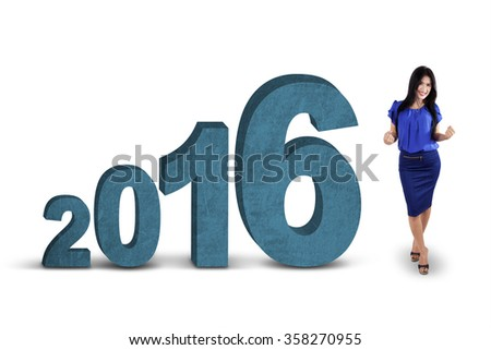 Successful female entrepreneur celebrating her success in the studio with numbers 2016, isolated on white background
