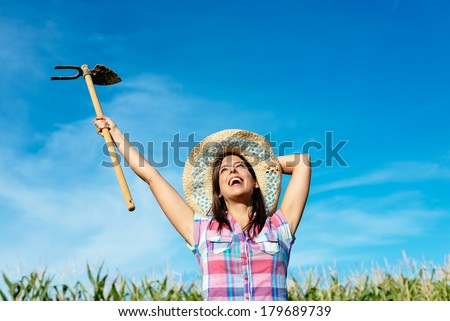 Successful female farmer raising hoe in corn field and smiling. Countryside blissful woman with work tool wearing straw hat and checkered shirt. - stock photo
