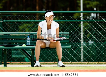 Successful female tennis player rests with bottle of water on the bench at the tennis court - stock photo