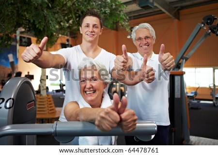 Successful fitness team in a gym holding thumbs up - stock photo