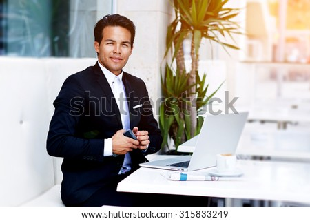 Successful freelancer man work remotely on his laptop computer while sitting at modern restaurant, confident businessman sitting at the table with open net-book and holding mobile phone in the hand - stock photo