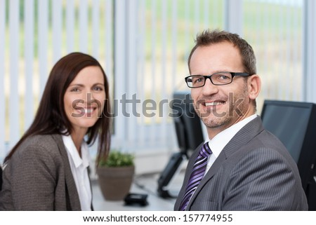 Successful friendly businessman wearing glasses sitting in the office having a meeting with a female coworker smiling at the camera - stock photo