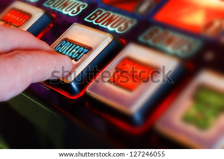 successful gambler collecting winnings from one armed bandit - stock photo